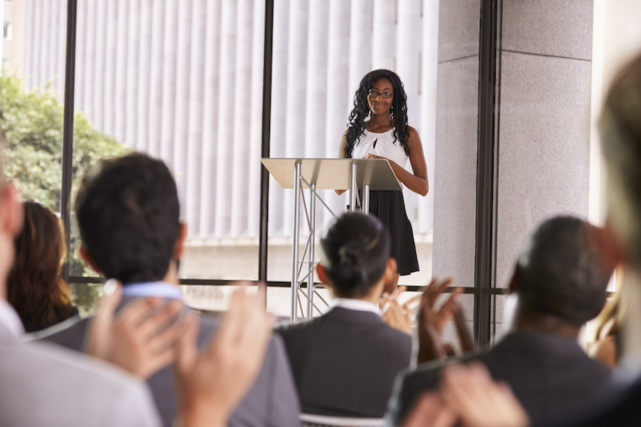 Young Black Women with lectern delivers great speech with confidence