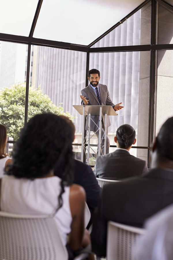 Hispanic Man Presents seminar with lectern