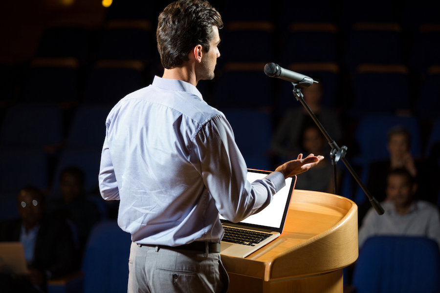 Male Business Executive giving speech from behind a lectern