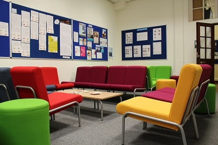 Staff room in school with sofas and noticeboards on walls