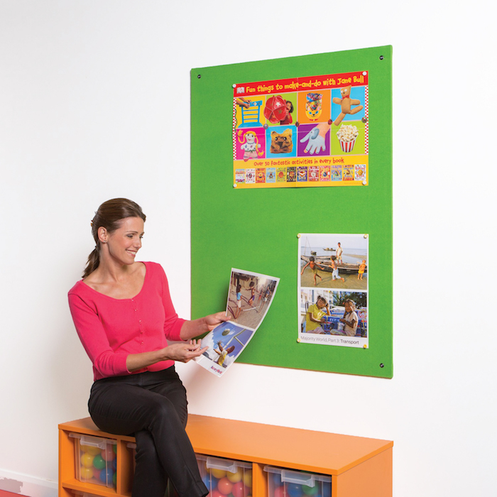 Teacher with an unframed notice board in bright green colour