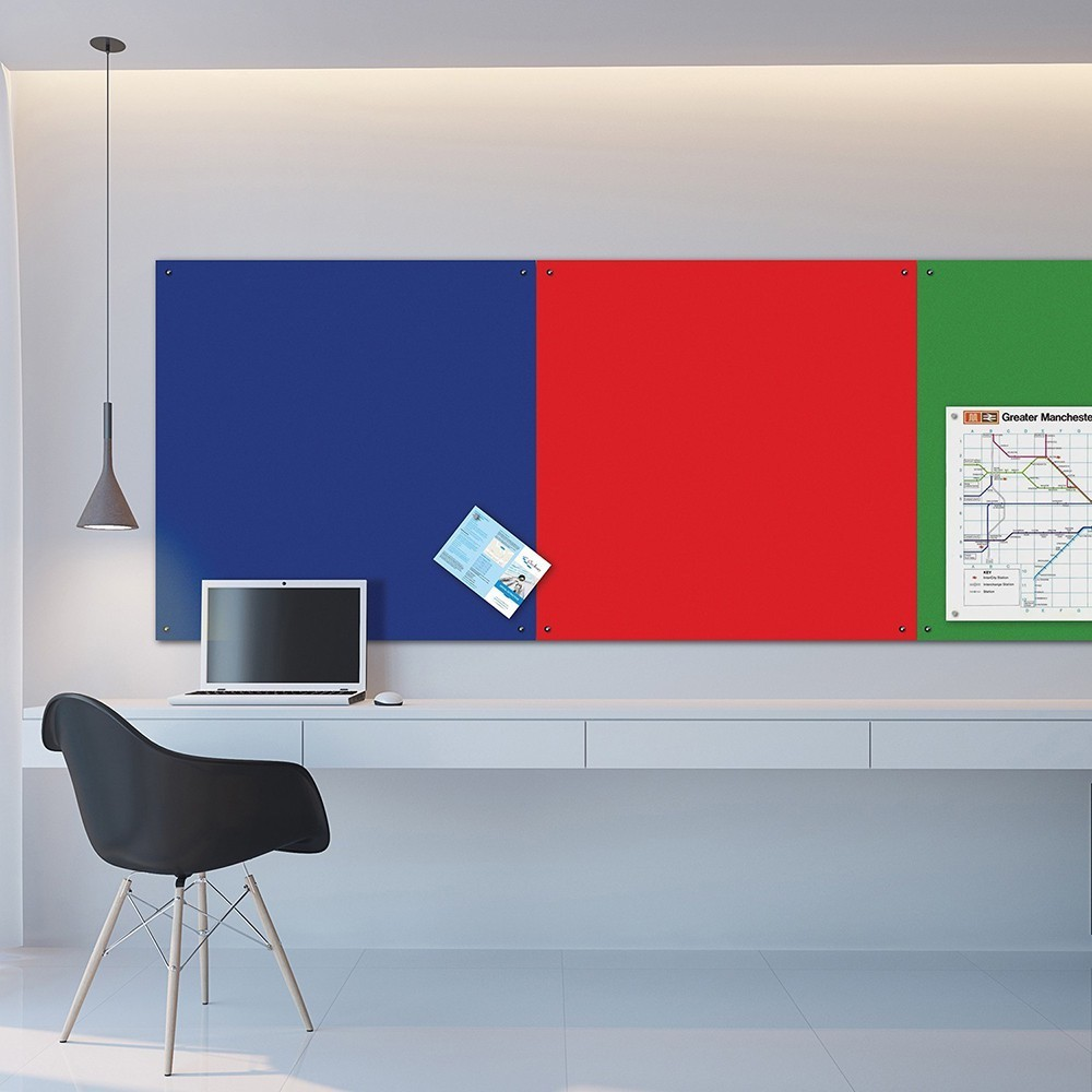 Office wall with numerous unframed notice boards linked up together to form a large notice board