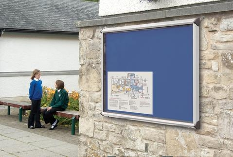 wall mounted outdoor notice board with school kids in background