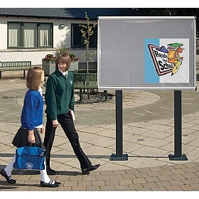 School Kids walking past an outdoor notice board in school
