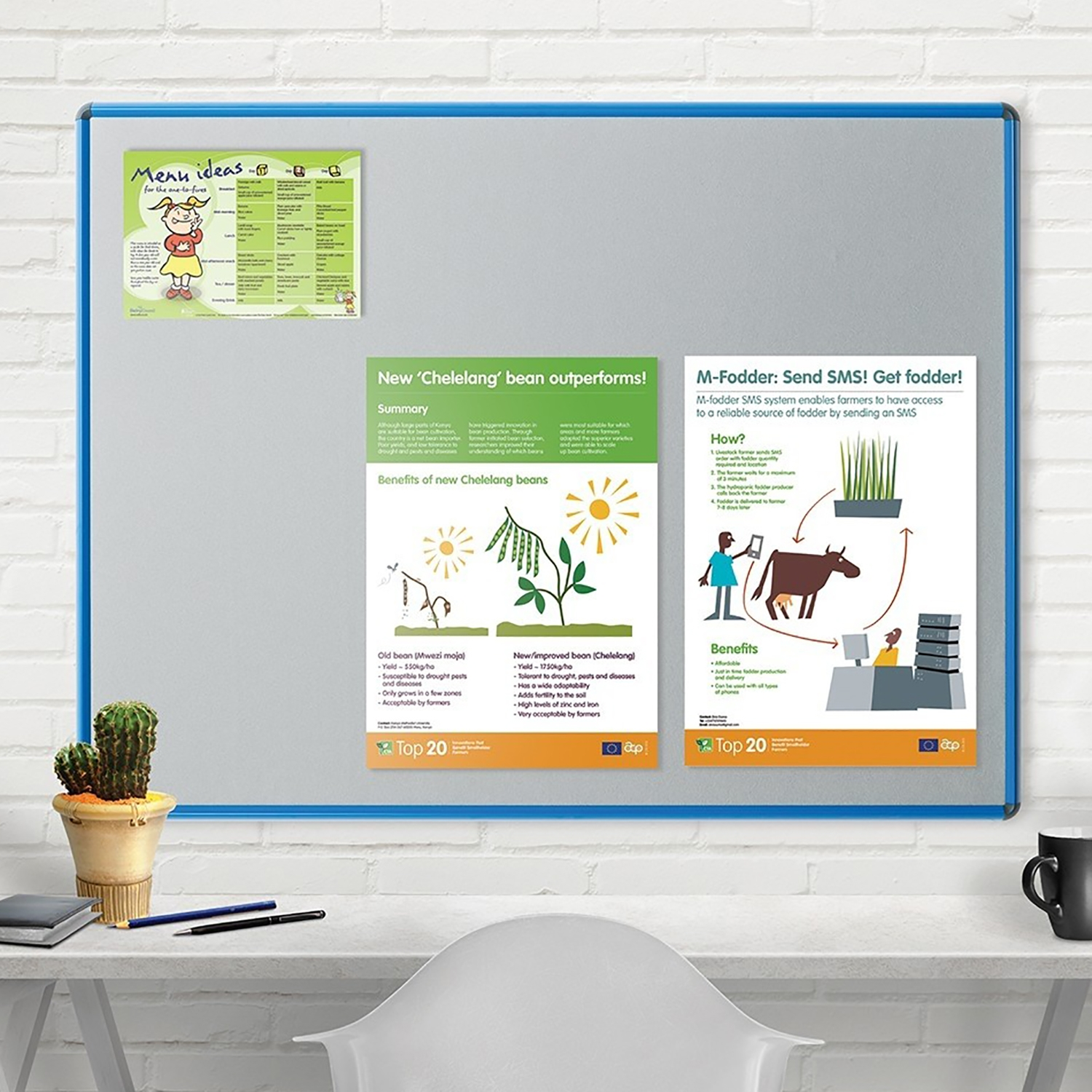 Shield Design Notice Boards - Product example notice board in office on wall with desk