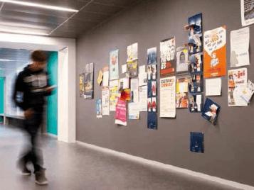 school corridor pupil walking past large notice board