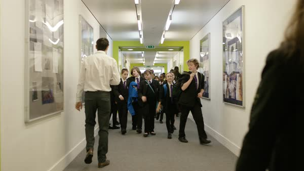 School Kids and Teacher In Corridor with Notice Boards on Wall