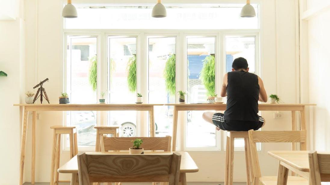 Inside modern coffee shop with customer at window seat