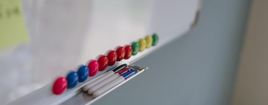 pen tray and magnets on a school whiteboard