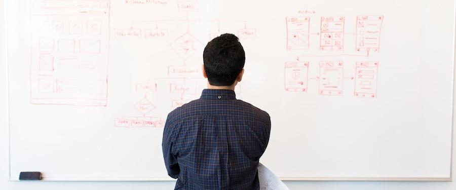 Guy in front of whiteboard looking at it and pondering